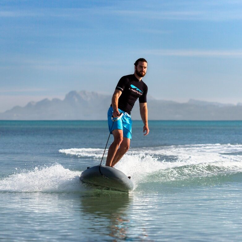 Man in a black Lampuga shirt riding on the ocean with mountains in the horizon